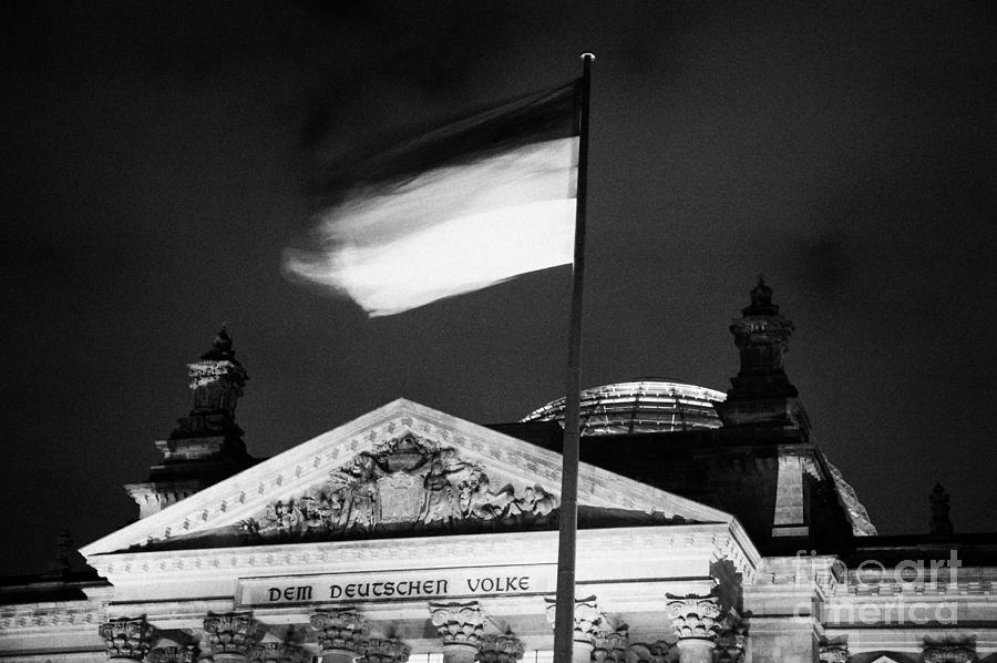 german flag flying fluttering on flagpole outside reichstag building Berlin Germany Photograph