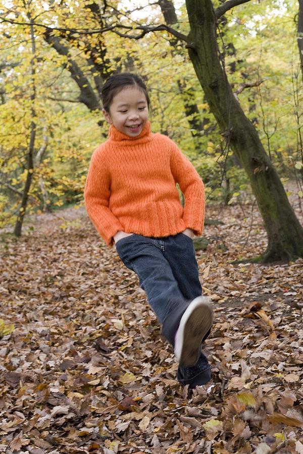 Girl Kicking Leaves Photograph