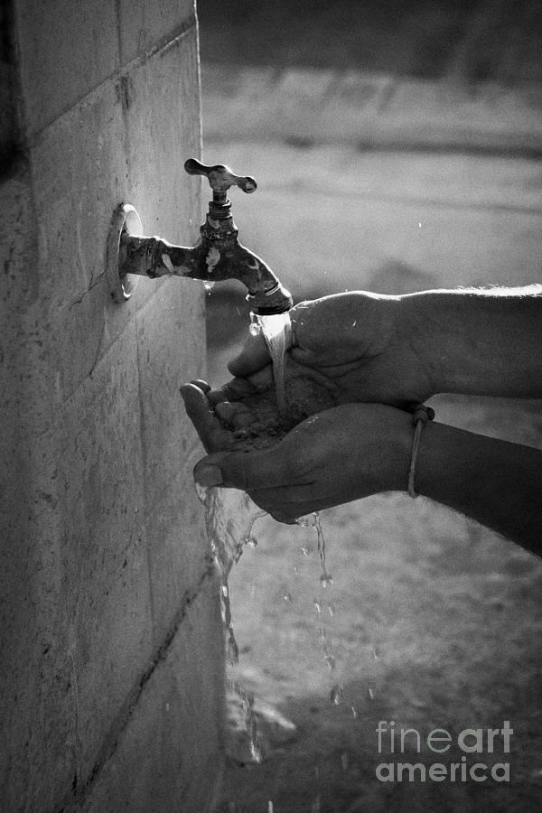 Hispanic Man Cupping Water And Washing Hands At Outdoor Tap Photograph  - Hispanic Man Cupping Water And Washing Hands At Outdoor Tap Fine Art Print