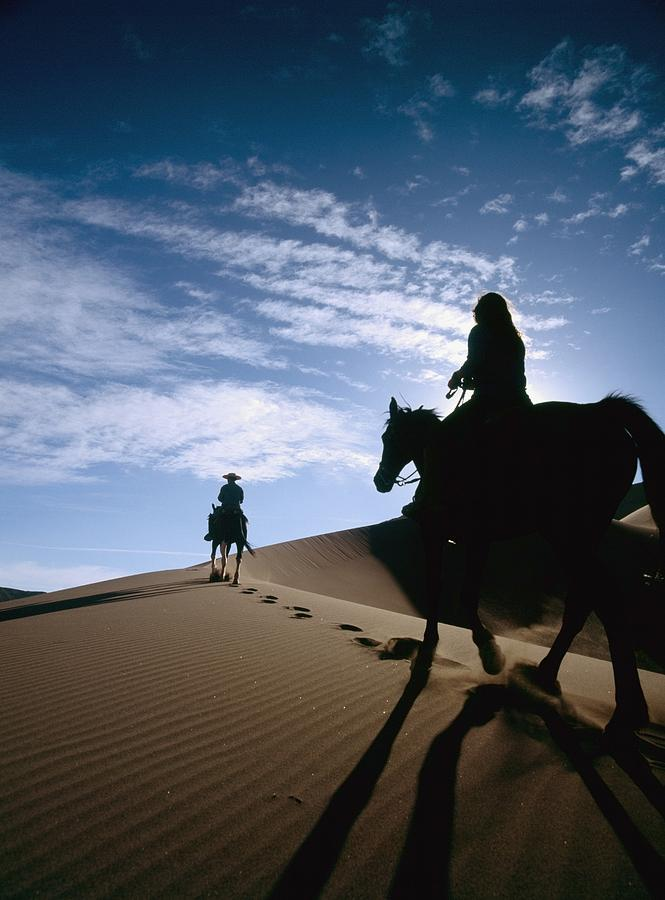 Horseback Riders In Silhouette On Sand Photograph