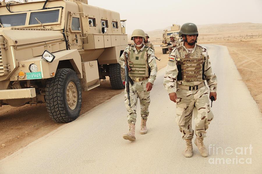 اكبر و اوثق موسوعة للجيش العراقي على الانترنت Iraqi-army-soldiers-walk-beside-an-mrap-stocktrek-images
