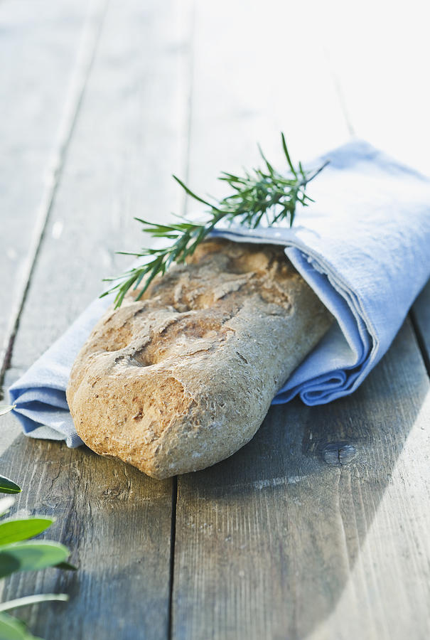 Italy, Tuscany, Magliano, Close Up Of Bread Loaf With Rosemary Wrapped In Napkin On Wooden Table Photograph
