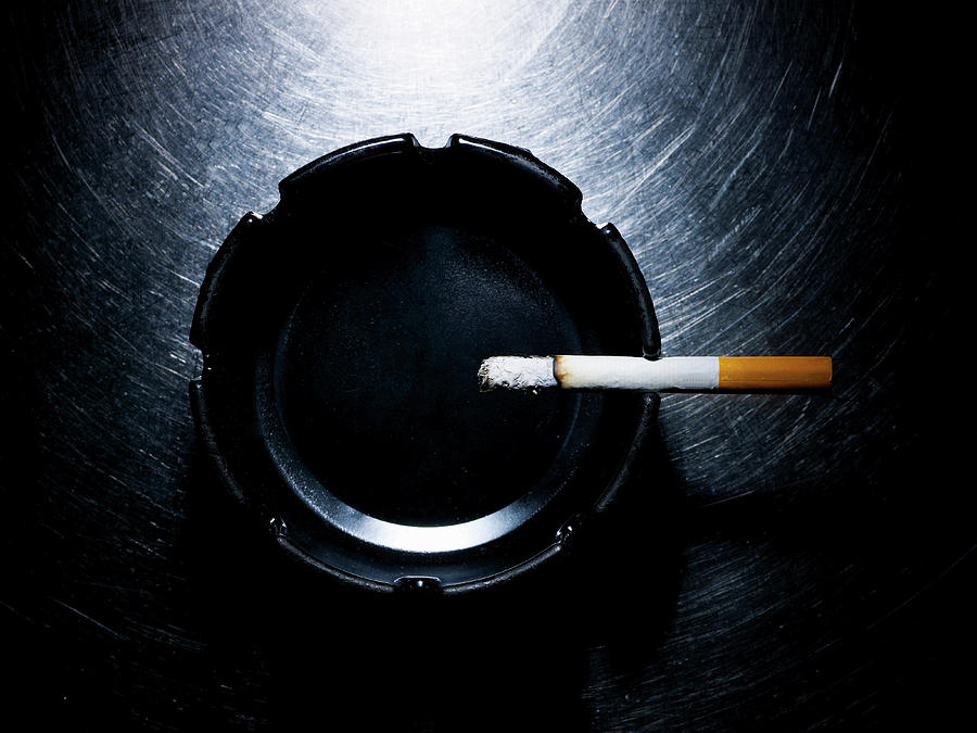 Lit Cigarette And Ashtray On Stainless Steel. Photograph