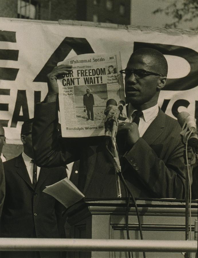 Malcolm X, Holding Up Newspaper Photograph