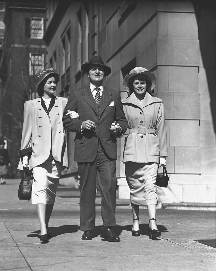 Man And Two Women Walking On Sidewalk, (b&w) Photograph