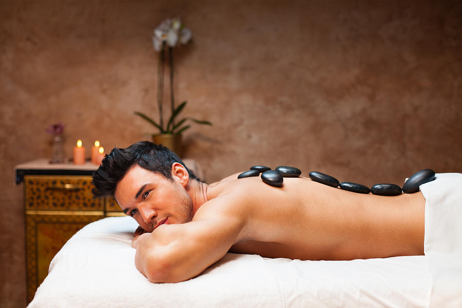 Man Having Lastone Therapy In Spa Center Photograph