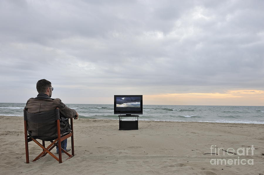 Man Watching Tv On Beach At Sunset Photograph