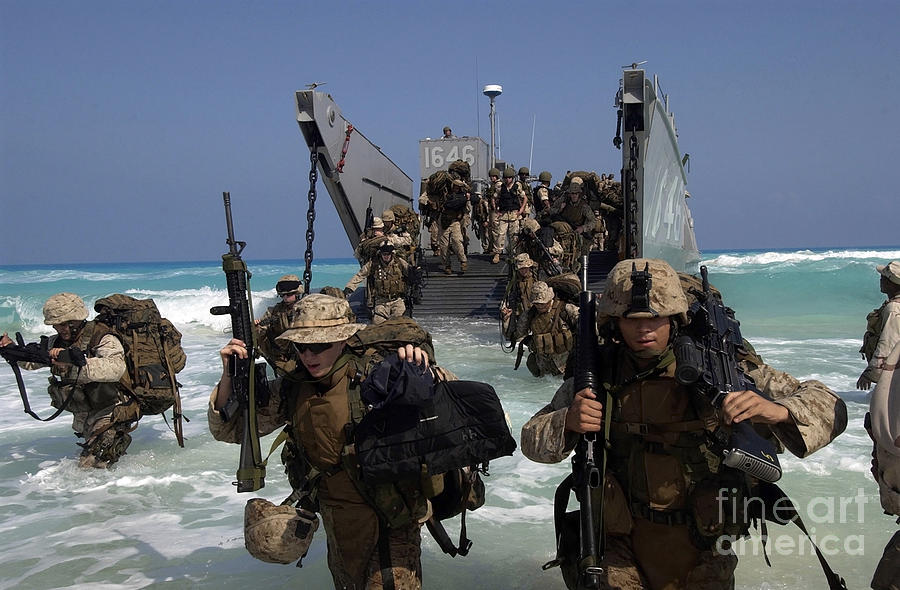 Marines Disembark A Landing Craft Photograph