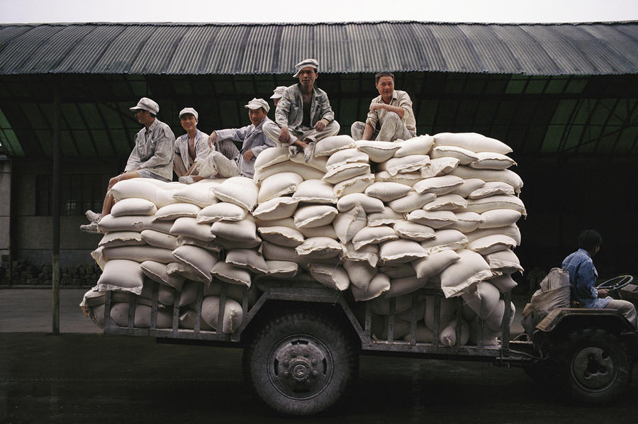 Men Sit On Bags Of Flour Photograph