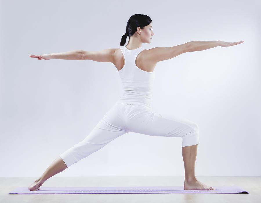 Mid Adult Woman Doing Yoga Against White Background Photograph