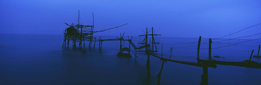 Water Photograph - Old Fishing Platform Over Water At Dusk by Axiom Photographic