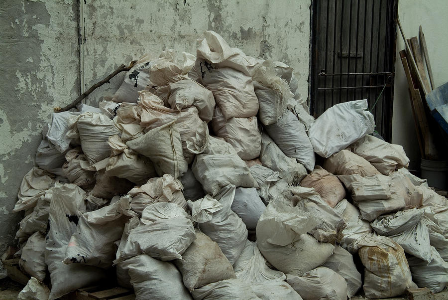 Pile Of Garbage Bags Against A Concrete by Todd Gipstein