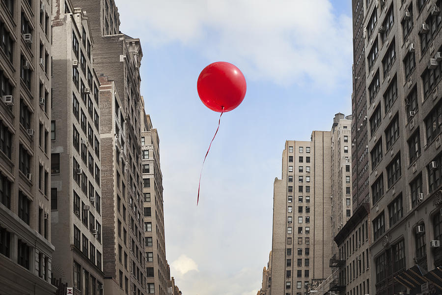 Red Balloon Floating Through City Photograph