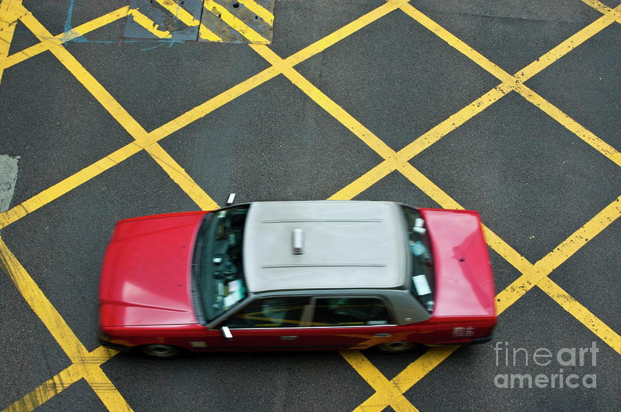Red Taxi Cab Driving Over Yellow Lines In Hong Kong Photograph  - Red Taxi Cab Driving Over Yellow Lines In Hong Kong Fine Art Print