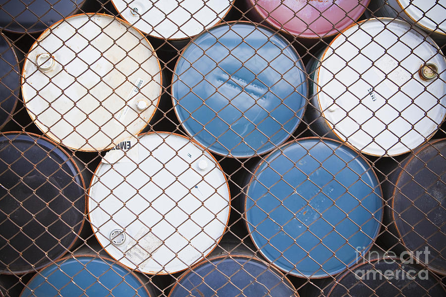 Rows Of Stacked Barrels Behind A Fence Photograph