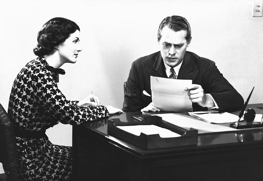 Secretary Assisting Businessman Reading Document At Desk, (b&w) Photograph
