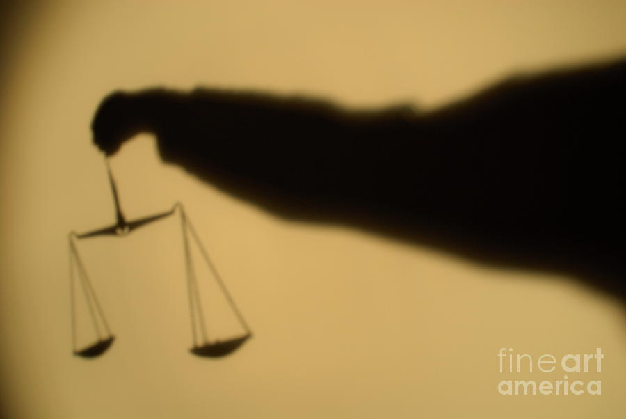 Shadow Of A Persons Arm Holding Out The Scales Of Justice Photograph