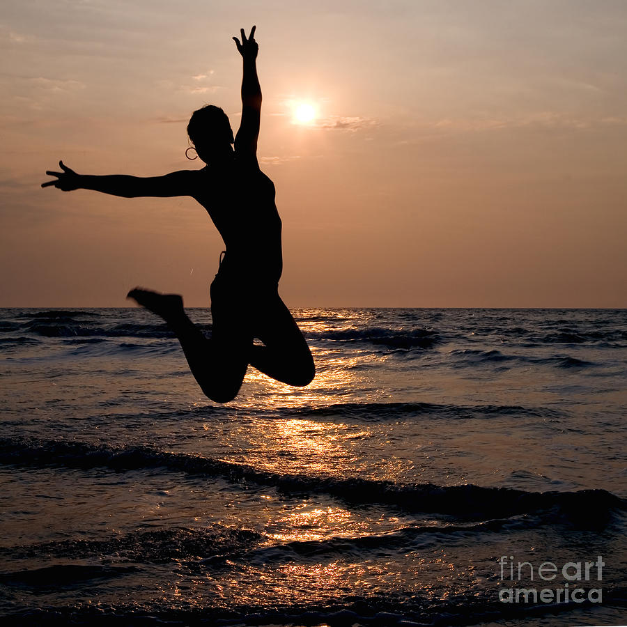 Silhouette Of A Girl Jumping In The Ocean At Sunset Photograph