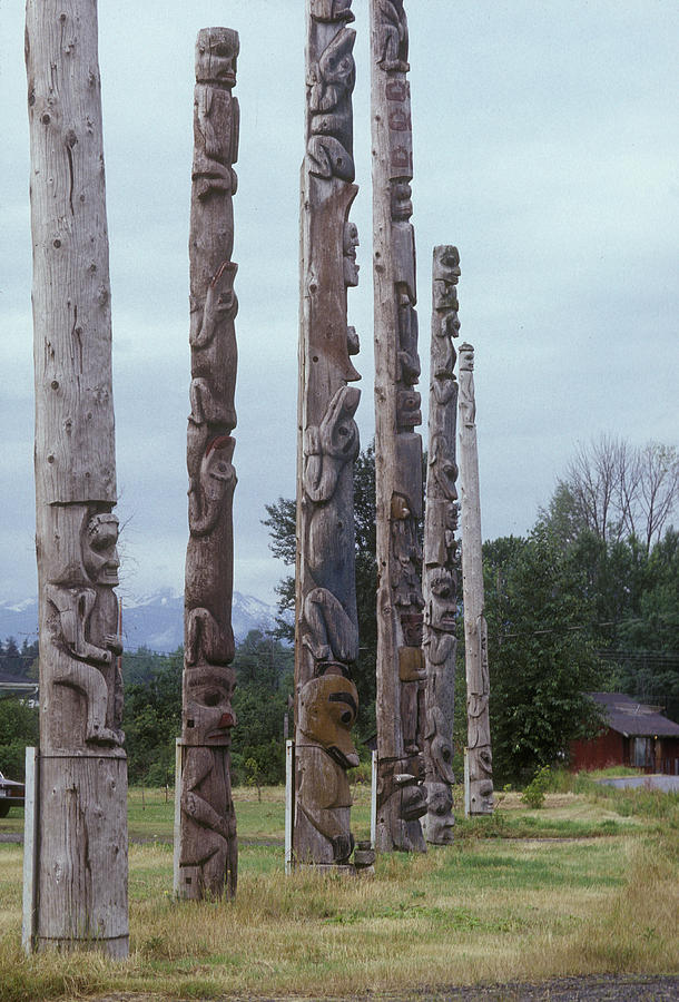 Six Wooden Totem Poles Stand In A Row Photograph  - Six Wooden Totem Poles Stand In A Row Fine Art Print