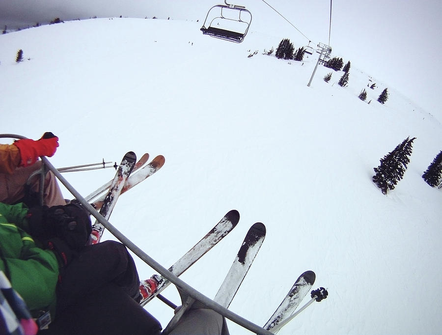 Skiers Sitting On Chairlift Photograph