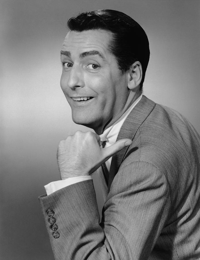 Smiling Man Pointing In Studio, (b&w), Portrait Photograph