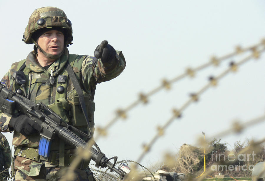Barbwire Photograph - Soldier Calls Out Approaching Locals by Stocktrek Images