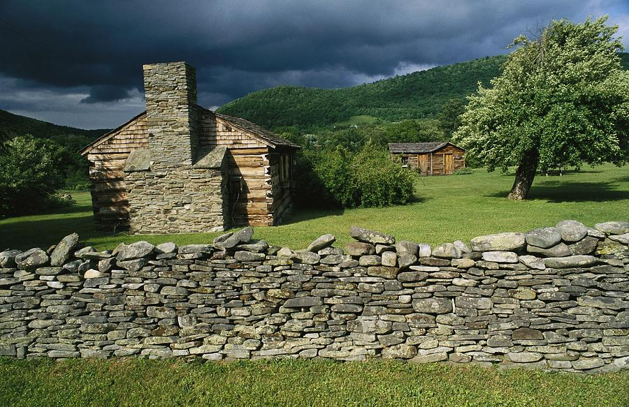 North America Photograph - Storm Clouds Form Above Log Buildings by Raymond Gehman