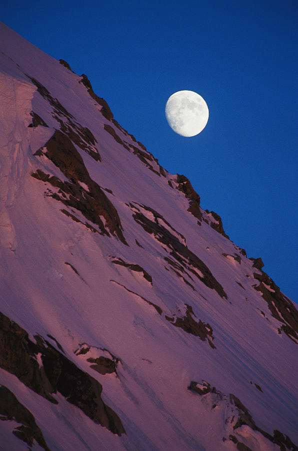 The Moon Rises Over A Snow-covered Photograph