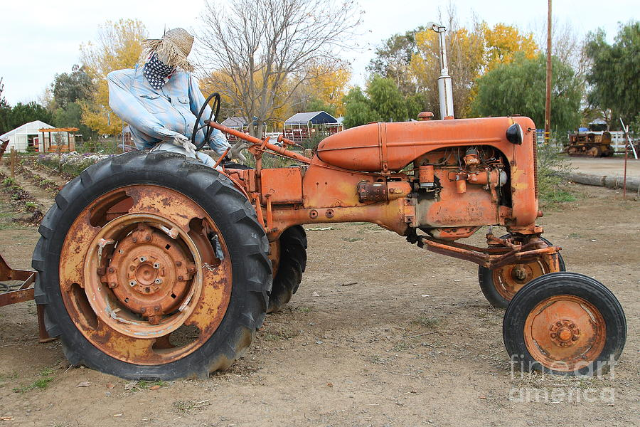 The Scarecrow Riding On The Old Farm Tractor . 7d10301 Photograph