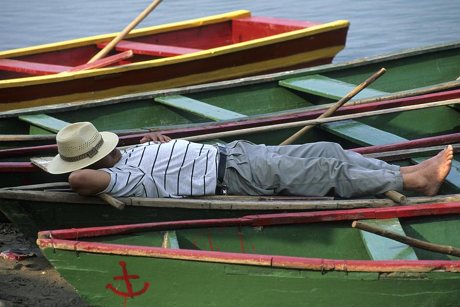 Tour Boat Guide Naps Amidst Rowboats Photograph
