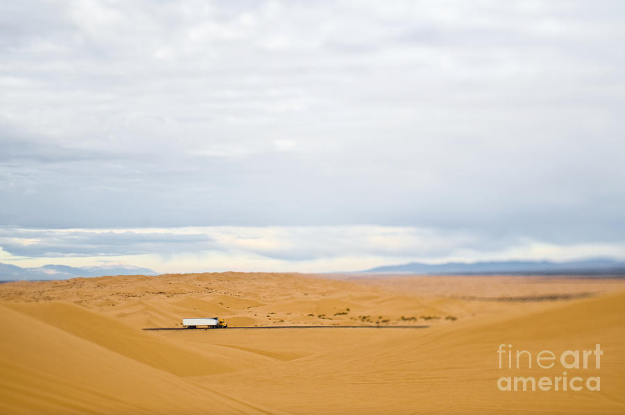 Truck Driving Through Desert Photograph