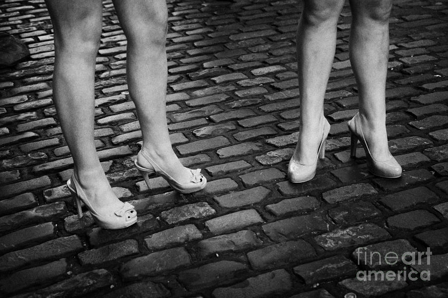 Two Young Women Wearing High Heeled Shoes And Fake Tan On Cobblestones On A Night Out In Dublin  Photograph