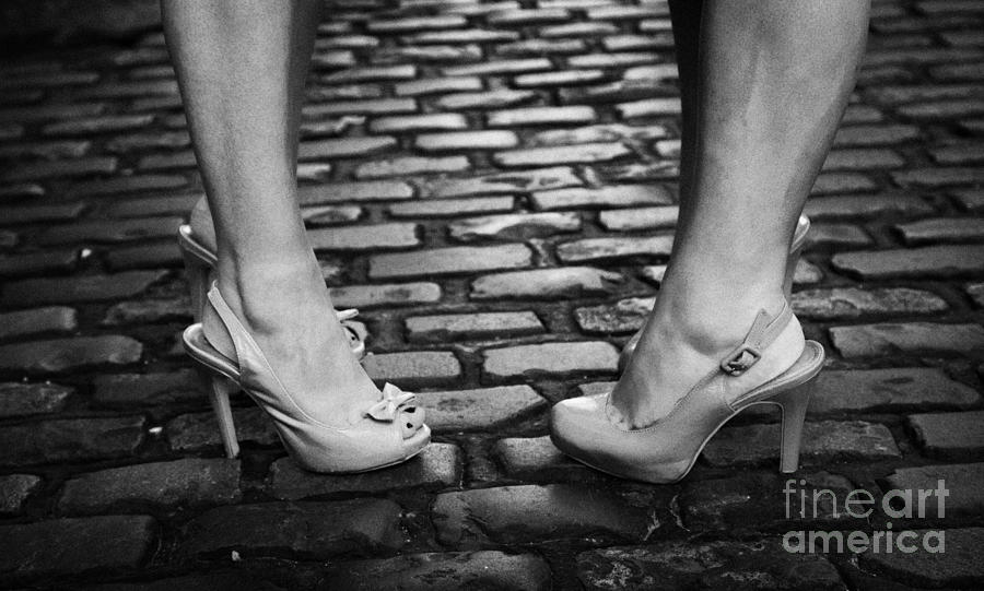 Two Young Women Wearing High Heeled Shoes And Fake Tan On Cobblestones On A Night Out Photograph