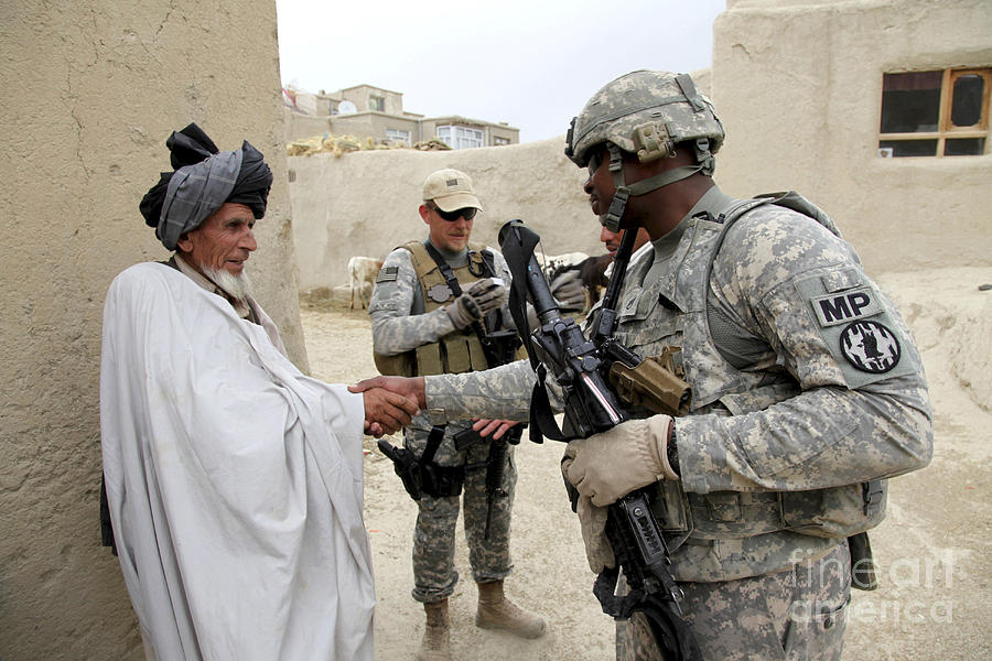 U.s. Army Soldier Shakes Hands With An Photograph