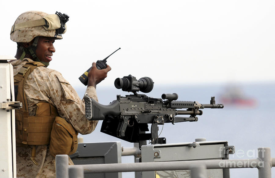 U.s. Marine Talks On A Radio While Photograph