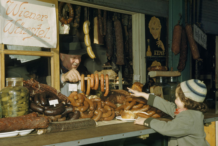 Vendor Holds Up Sausages For Young Girl Photograph
