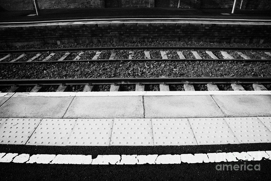 Railway Photograph - Warning Line And Textured Contoured Tiles Railway Station Platform And Track Northern Ireland by Joe Fox