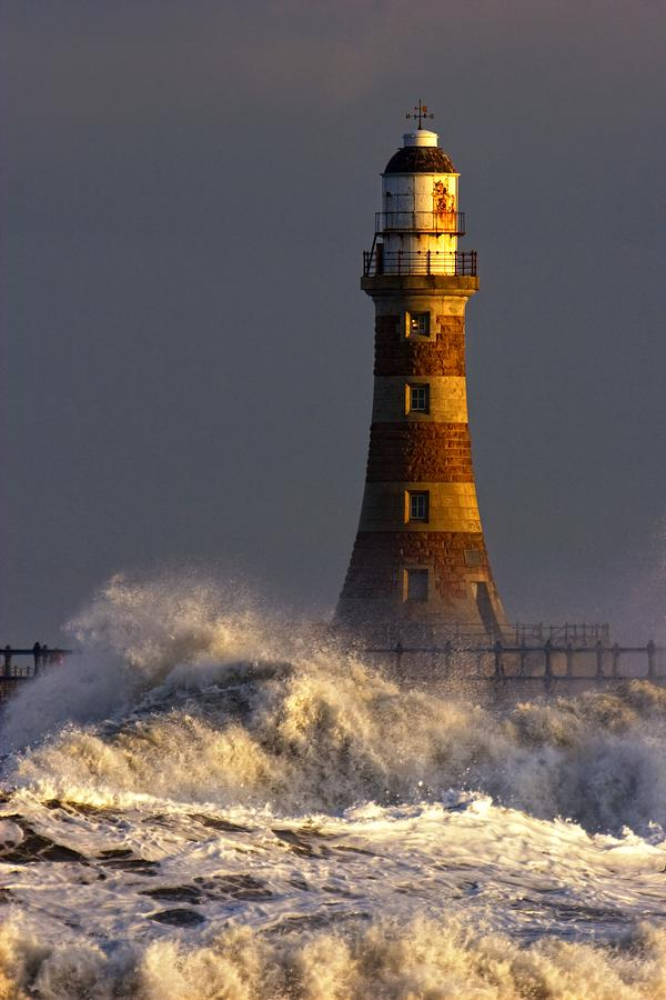 Waves Crashing Against A Lighthouse Photograph by John Short
