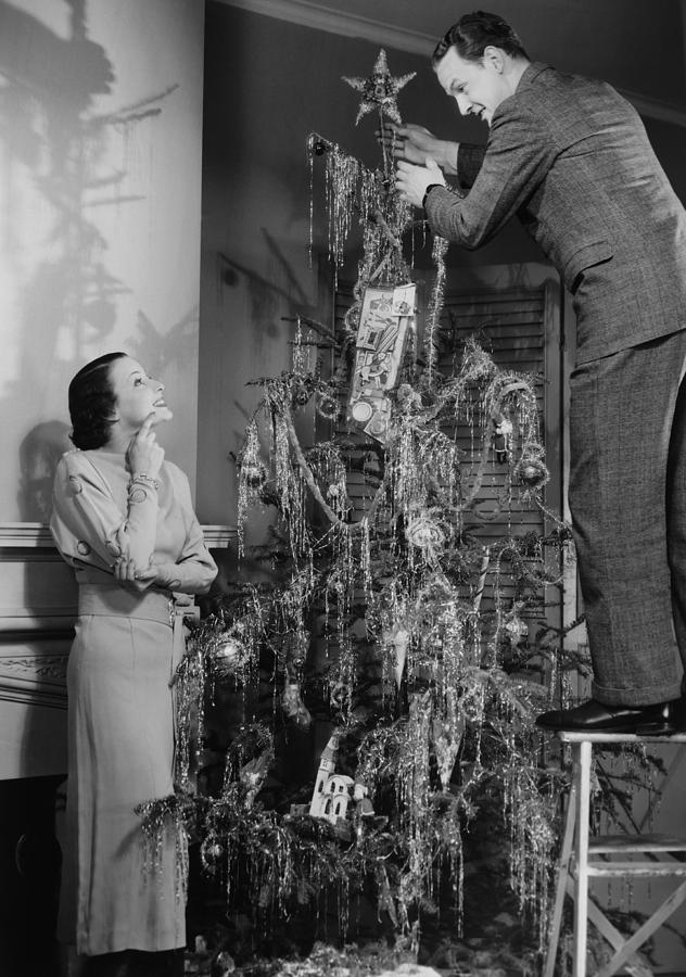Woman Assisting Man Placing Star On Top Of Christmas Tree, (b&w) Photograph