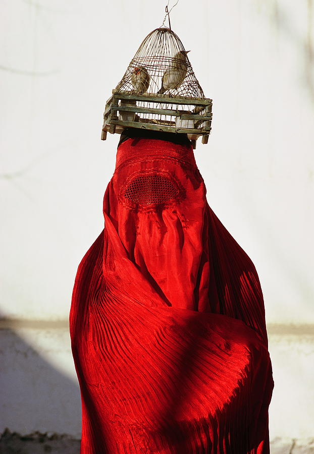 Woman Draped In Red Chadri Carries Photograph