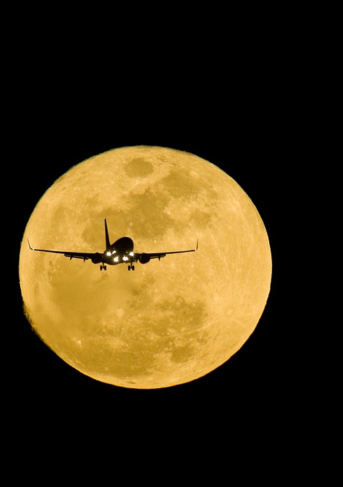 Aeroplane Silhouetted Against A Full Moon Print by David Nunuk