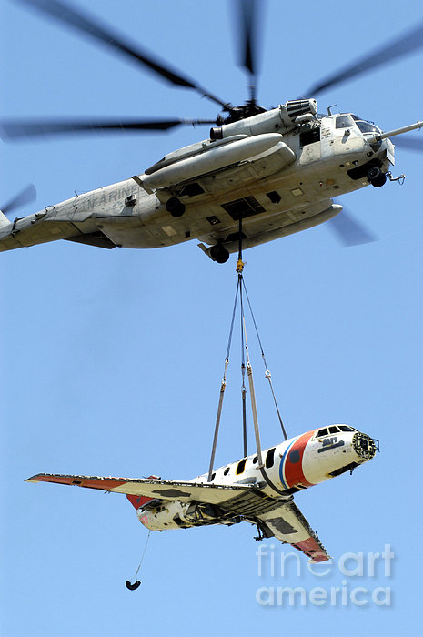 A Ch-53 Sea Stallion Lifts A Hu-25 Print by Stocktrek Images