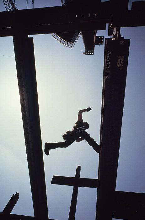 A Construction Worker Jumps From Girder Print by Lynn Johnson