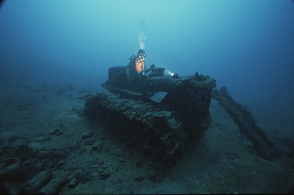 A Diver Inspects A Tractor Dumped Print by David Doubilet