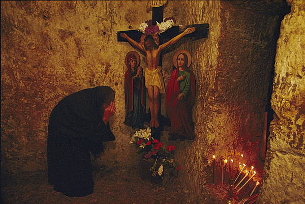 A Greek Pilgrim Prays In The Grotto Print by Annie Griffiths