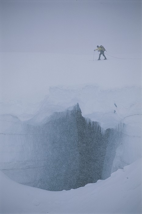 A Skier Above A Deep Glacier Crevasse Print by John Burcham