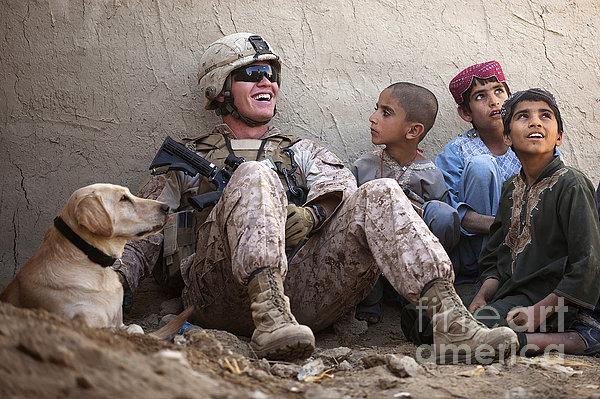 A U.s. Marine Jokes With Afghan Print by Stocktrek Images