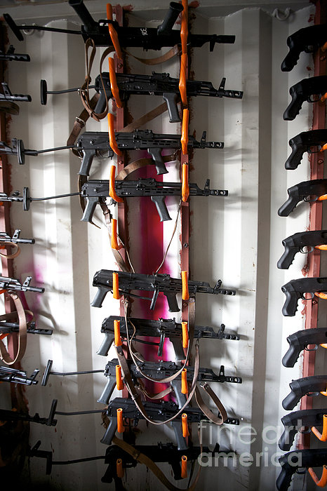 Akm Assault Rifles Lined Up On The Wall Print by Terry Moore