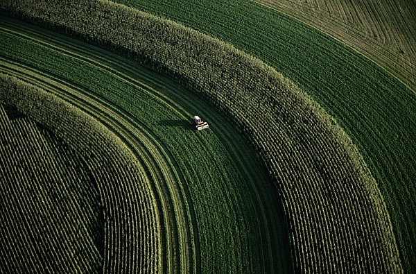 An Aerial View Of A Tractor On Curved Print by Paul Chesley