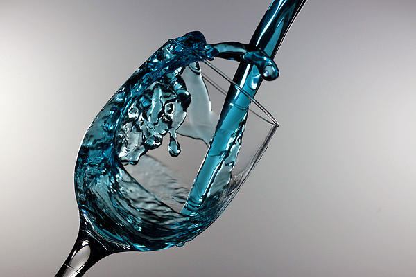 Blue Martini Splashing From A Wine Glass Print by Paul Ge